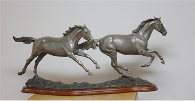 Bronze sculpture of horses galloping, titled Running Free